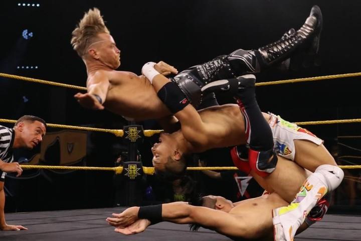 アトラスを丸め込みながらマーベリックにジャーマン・スープレックスを放つ離れ技を披露したKUSHIDA。(C)2020 WWE,Inc. All Rights Reserved.
