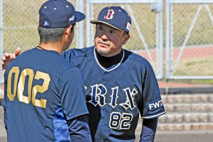 育成の谷岡楓太投手にアドバイスを送り、肩をたたいて激励する入来投手コーチ(入来コーチが短い時間、マスクを外した時に撮影)。写真:北野正樹