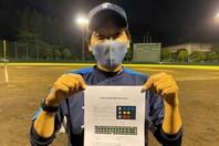飯能市民球場にて、自作のテキストを笑顔で掲げる宮田コーチ。図の多い形式や柔らかな文体から優しさが伝わってくる。写真:球団提供