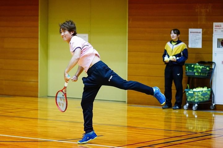 キレッキレのスライスサービスで参加者を驚かせた西岡。後ろは津幡町テニス協会スタッフの河内さん。写真:山崎賢人(THE DIGEST写真部)